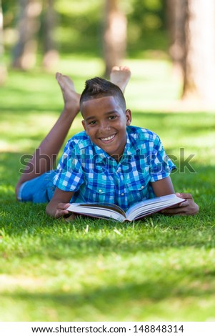 Outdoor portrait of student black boy reading a book - African people - stock photo