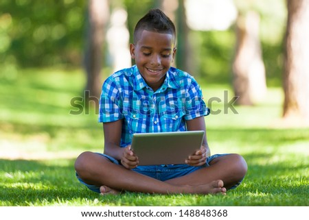 Outdoor portrait of student black boy using a tactile tablet - African people - stock photo