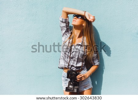 Outdoor portrait of stylish photographer girl holding vintage retro camera,wearing bright trendy sunglasses and jacket,amazing view of city from the roof.Toned,lifestyle,accessorize,hiker