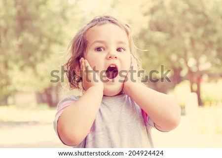 outdoor portrait of surprised cute child girl on natural background - stock photo