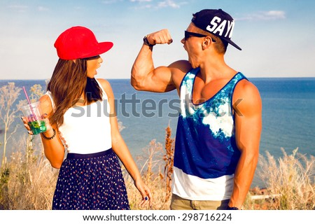 Outdoor portrait of tanned friends,drinking cocktail after fitness training.Handsome man shows her girlfriend his big muscles.Hipster Girl surprised of her boyfriend,fitness couple,friends training - stock photo