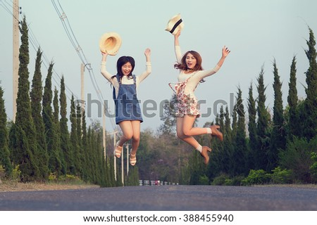 Outdoor portrait of teenage asian girls wearing a hat and jump on the road, vintage tone - stock photo