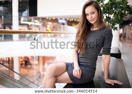 Outdoor portrait of the beautiful young sexy woman. Attractive caucasian  girl is in the shop. Pretty female posing - stock photo