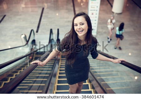 Outdoor portrait of the beautiful young sexy woman. Attractive caucasian  girl smiling and posing in the shop. Pretty female person with positive emotions - stock photo