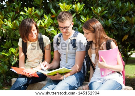 Outdoor portrait of three smiling students - stock photo
