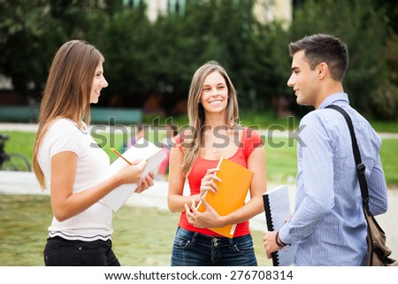 Outdoor portrait of three students talking in a park - stock photo