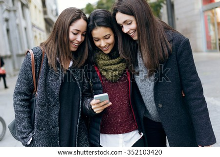 Outdoor portrait of three young beautiful women using mobile phone. - stock photo