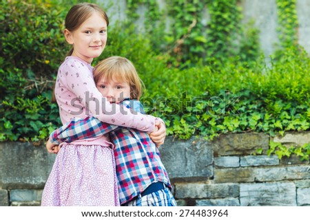 Outdoor portrait of two adorable kids, big sister and her little brother hugging each other - stock photo