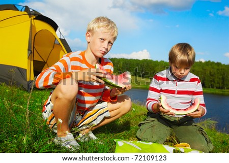 outdoor portrait of two boys eating watermelon on green grass near camp