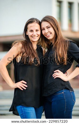 Outdoor portrait of two cute yang sisters. - stock photo