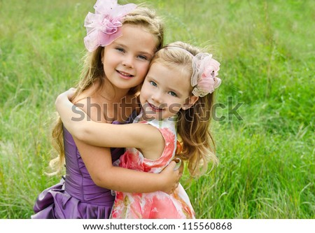 Outdoor portrait of two embracing cute little girls - stock photo