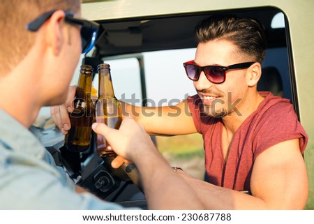 Outdoor portrait of two friends toasting with bottles of beer in car. - stock photo