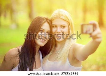 Outdoor portrait of two girl friends taking photos with camera - stock photo