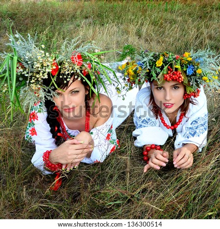 Outdoor portrait of two sisters in wreath - stock photo