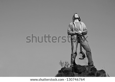 Outdoor portrait of vintage styled guitar man. - stock photo