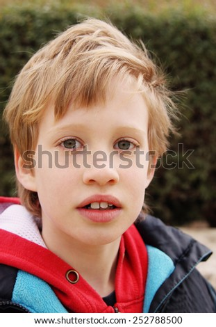 Outdoor portrait of 7 years old boy - stock photo