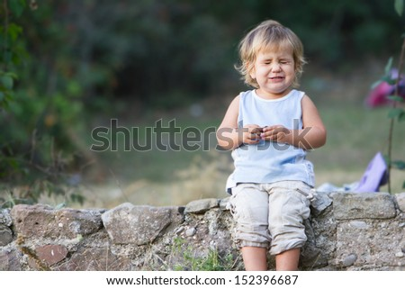 outdoor portrait of young baby girl making faces