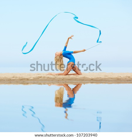 outdoor portrait of young beautiful blonde woman gymnast exercising with ribbon on the beach