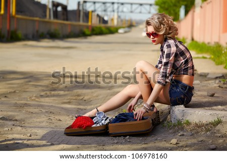 outdoor portrait of young beautiful blonde woman hitchhiker sitting on the roadside  with clothes in opened suitcase - stock photo
