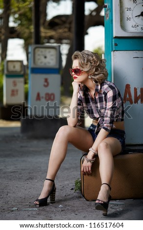 outdoor portrait of young beautiful blonde woman on gas station sitting on her travelling suitcase near gas pump - stock photo