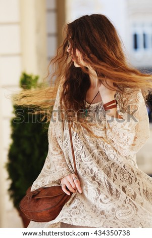 Outdoor portrait of young beautiful happy rotating lady. Long hair flying in the wind. Model wearing stylish summer lace dress. Female fashion. Sunny day. City lifestyle. Waist up