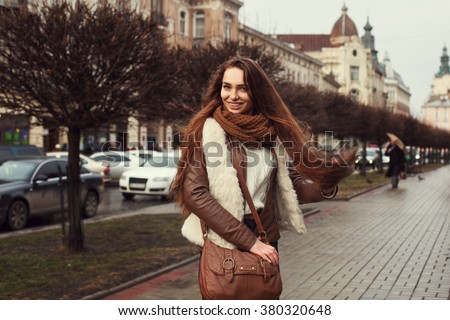 Outdoor portrait of young beautiful smiling lady wearing stylish clothes standing on the street. Model looking at camera. Female fashion concept.