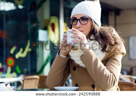 Outdoor portrait of young beautiful woman drinking coffee. - stock photo