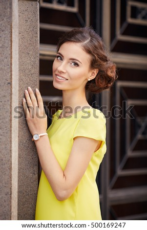Outdoor portrait of young beautiful woman fashion model in yellow dress on entrance background