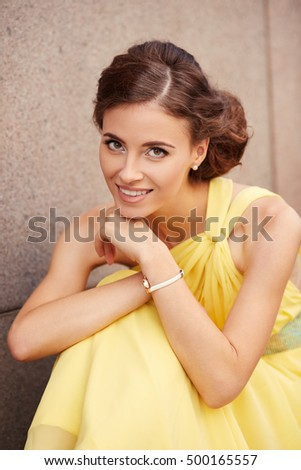Outdoor portrait of young beautiful woman fashion model in yellow dress on granite wall background