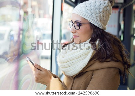 Outdoor portrait of young beautiful woman using her mobile phone on a bus.
