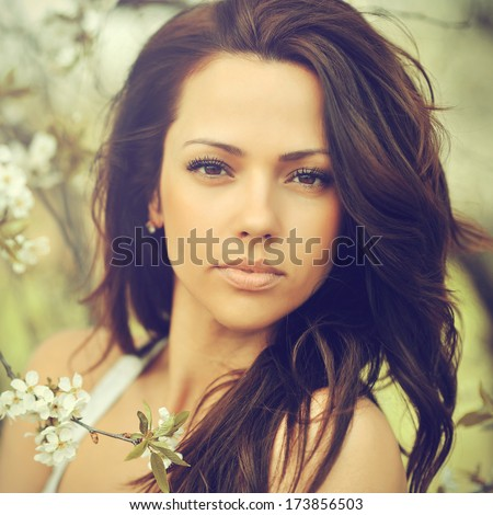 Outdoor portrait of young beautiful woman with chic curly brown hair and perfect skin