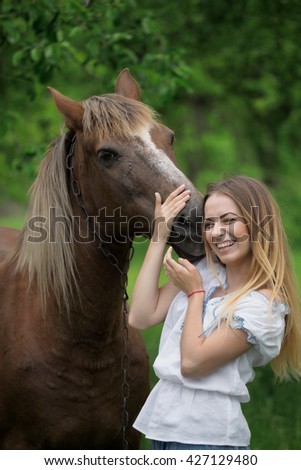 outdoor portrait of young beautiful woman with horse.