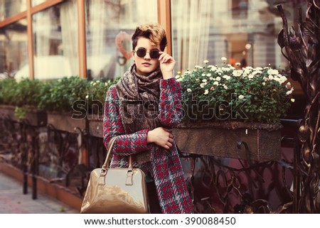 Outdoor portrait of young beautiful woman with round sunglasses. Model holding her glasses and looking at camera. Bob short hair. Female street fashion. City lifestyle. Toned - stock photo