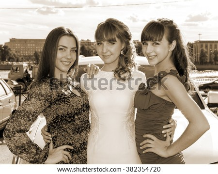 Outdoor portrait of young bride with her female friends in retro style - stock photo
