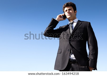 Outdoor portrait of young businessman talking with smartphone