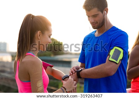 Outdoor portrait of young couple using they smartwatch after running.