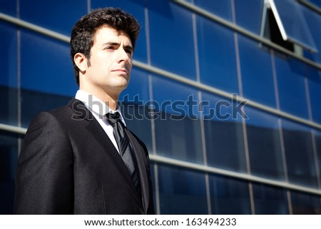 Outdoor portrait of young executiva man looking at the horizon