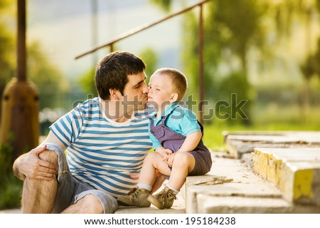 Outdoor portrait of young father kissing his little son - stock photo