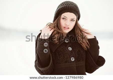Outdoor portrait of young girl in winter park. Woman sitting in snow field in cold weather. - stock photo