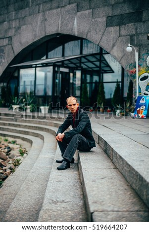Outdoor portrait of young handsome bald male businessman in suit in front of modern building. business trip concept