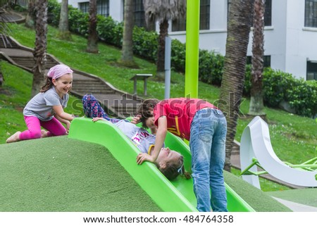 outdoor portrait of young happy child girl having fun on playground