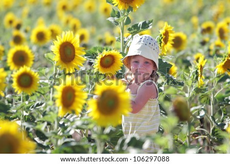 outdoor portrait of young happy child girl in sunflower field - stock photo
