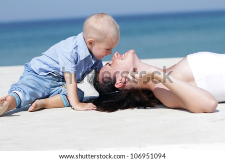 outdoor portrait of young happy mother and child on natural background - stock photo