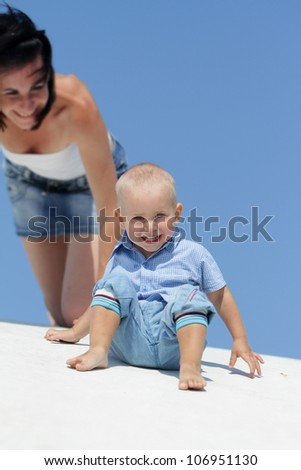 outdoor portrait of young happy mother playing with child isolated over blue sky background - stock photo