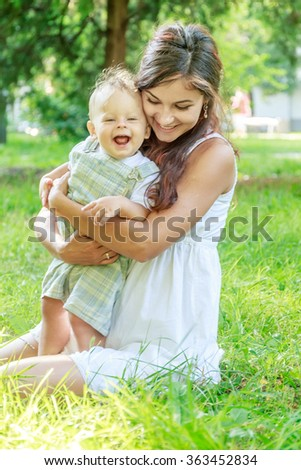 outdoor portrait of young happy smiling mother with her baby son having fun on natural background