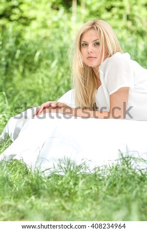 outdoor portrait of young happy woman relaxing on natural background