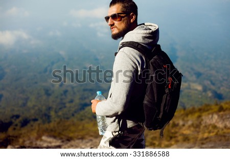 Outdoor portrait of Young man hiking on the mountains,smiling happy portrait of tourist male.extreme sport,sport equipment,travel bag,Caucasian Male hiker walking in forest,drinking water,Norway,UK - stock photo