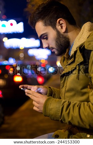 Outdoor portrait of young man using his mobile phone at night. - stock photo