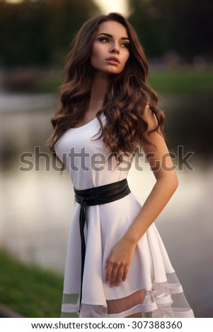 Outdoor portrait of young pretty beautiful calm woman posing outdoors in park in the evening. Elegant sexy girl wearing white summer dress. - stock photo