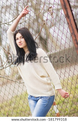 Outdoor portrait of young pretty beautiful woman in cold spring weather in park. Sensual brunette posing and having fun
